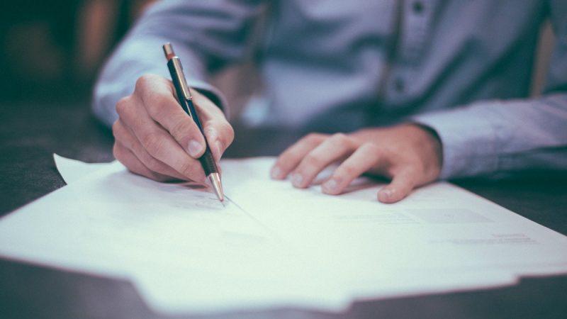 Mężczyzna piszący na kartce
