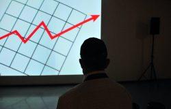 Mężczyzna stojący przed wykresem ekonomicznym