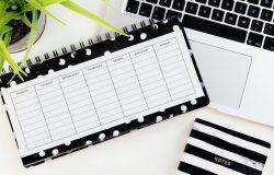 Kalendarz, komputer i notes na biurku