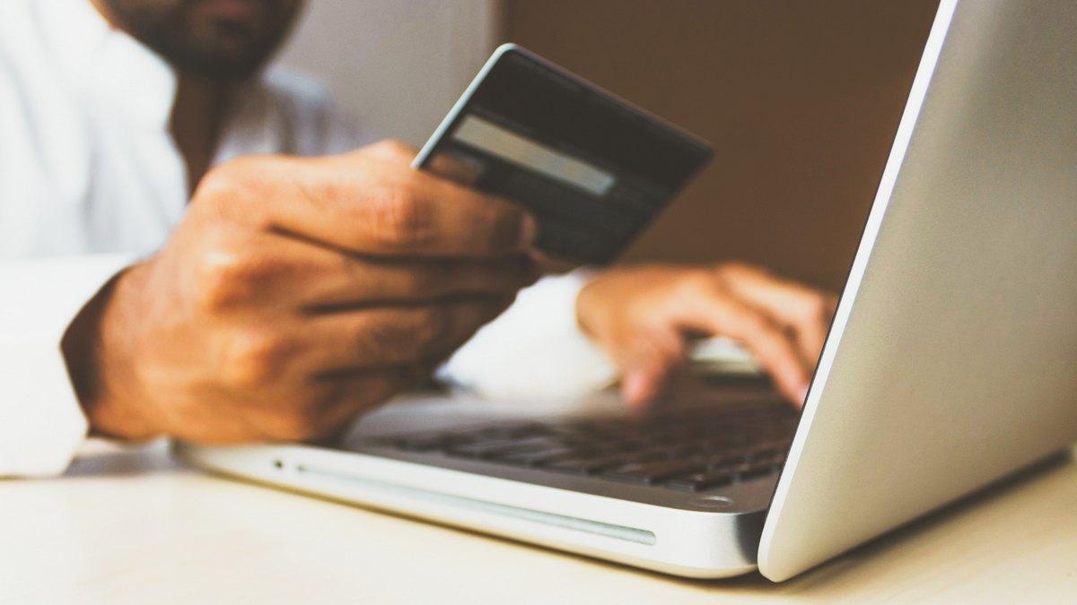 Mężczyzna z kartą kredytową przed laptopem